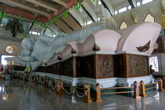 Gigantic white marble reclining Buddha In Buddhism sacred hall of Wat Pha Phu Gon temple stock image