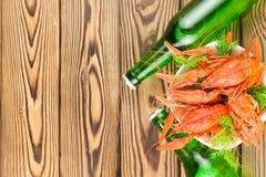 Udział gotowani czerwoni crayfishes i zielony świeży koper w białym ceramicznym pucharze obok dwa pełnych butelek piwo zdjęcie stock