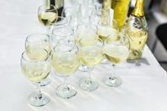 Udział zamazani szkła z szampanem na recepcyjnego przyjęcia stole zdjęcia stock