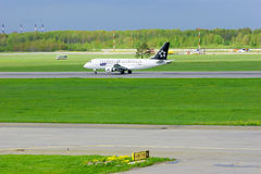 UDZIAŁU (Star Alliance liberia) połysk linii lotniczych Embraer ERJ-170 samolot w Pulkovo lotnisku międzynarodowym w Petersburg,  Fotografia Stock