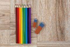 Udziały asortowani kolorów ołówki, gumki na drewnianym tle i Zdjęcie Royalty Free