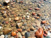 Udziały błyszczący kamienie w wodzie przy morzem Obraz Royalty Free