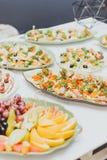 Udziały różny jedzenie przy przyjęciem, zakończeniem w górę, kanapkami z mięsem i owoc, zdjęcie stock