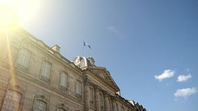UE de ondulação da bandeira do alargamento cinemático da luz solar acima da construção vídeos de arquivo