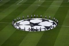Uefa Champions League logo over the grass of Santiago Bernabeu s. MADRID, SPAIN - FEBRUARY 17, 2017: top view of guys around Uefa Champions League logo on the stock photos
