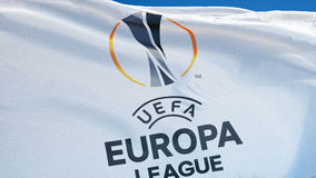 UEFA Europa League flag in slow motion seamlessly looped with alpha. UEFA Europa League flag waving in slow motion against clean blue sky, seamlessly looped stock footage