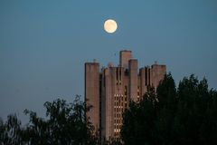 Uenusually large moon over the skyscraper in a summer evening sky. Moscow,Russia royalty free stock photography