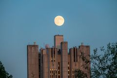 Uenusually large moon over the skyscraper in a summer evening sky. Moscow,Russia royalty free stock images
