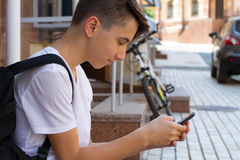 Äußeres Porträt des jugendlich Jungen Tragender Rucksack des hübschen Jugendlichen auf einer Schulter und dem Lächeln, telefonisc Stockfoto