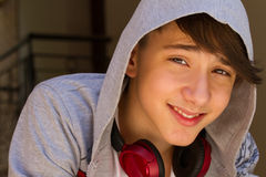 Äußeres Porträt des jugendlich Jungen Tragender Rucksack des hübschen Jugendlichen auf einer Schulter und dem Lächeln, telefonisc Lizenzfreie Stockfotografie