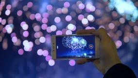 UF vicino del telefono che registra un video dei fuochi d'artificio stock footage