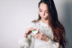 UFA, RÚSSIA - 14 DE JANEIRO DE 2018: A moça esperta resolve o enigma em um fundo branco, mantém disponível o cubo de um Rubik fotos de stock