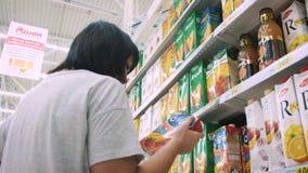 UFA RÚSSIA - 30 08 2017: A mulher escolhe o suco no supermercado Mulher que escolhe produtos no shopping Suportes da menina video estoque