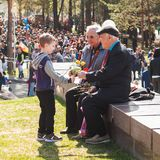 Ufa, Rússia-pode 09: o menino dá flores aos veteranos de guerra Parada da vitória Imagem de Stock Royalty Free