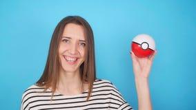 Ufa, Rusia - 7 de julio: Mujer joven que lleva a cabo un pokeball en su mano Pokemon va juego, el 7 de julio de 2017 en Ufa, Rusi almacen de video