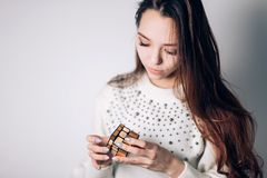 UFA, RUSSIA - JANUARY 14, 2018: A beautiful brunette woman in a white sweater collects a puzzle, a mirror Golden Rubik`s cube on royalty free stock photo