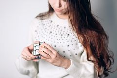 UFA, RUSSIA - JANUARY 14, 2018: Girl with long hair collects puzzle Rubik`s cube on white background, focus on hands stock photo