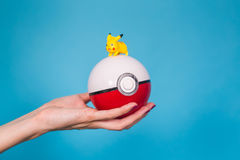 Ufa, Russia - July 8, 2017: woman`s hand holding pokeball with pikachu. pokemon go multiplayer game with elements of. Ufa, Russia - July 8, 2017: woman holding royalty free stock photography