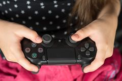 Hand girl playing Sony Dualshock 4. UFA, RUSSIA - NOVEMBER 12, 2017: Hand girl playing Sony Dualshock 4 controller for PlayStation 4 pro. Sony PlayStation 4 pro Royalty Free Stock Photography