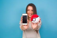 Ufa, Russland - 8. Juli 2017: Frau, die pokeball mit pikachu hält pokemon gehen spiel Multispieler Stockfotografie
