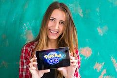 Ufa, Russland - 29. Juli: Frauenshow die Tablette mit Pokemon gehen Logo, am 29. Juli 2016 in Ufa, Russland stockfotografie