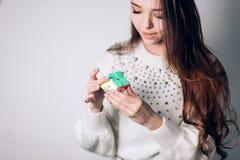 UFA RYSSLAND - JANUARI 14, 2018: En attraktiv brunettkvinna med långt hår löser ett pussel, en dubbelsidiga Rubiks kub på ett vit fotografering för bildbyråer