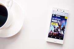 Ufa Ryssland - mars 15, 2019: startsida av Fortnite den modiga platsen på den Android smartphoneskärmen, telefonen och kaffekoppe royaltyfria foton