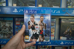 UFC 2. Bratislava, Slovakia, circa april 2017: Man holding UFC 2 videogame on Sony Playstation 4 console in store Stock Photo