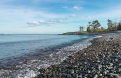 Ufer-Szene voll von Kieseln in der Küstenlinie Lizenzfreies Stockbild