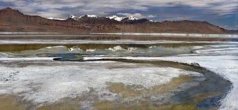 Ufer von Tso Kar See mit Steinsalzschalen und blauer Bogen der Biegung von Fluss, im Hintergrund ein Panorama des hohen braunen B Lizenzfreies Stockfoto
