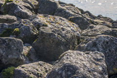 Uferdamm mit großen Felsen Stockfotografie