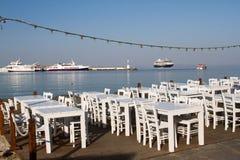 Ufergegend, die mit weißen Tabellen und Stühlen speist Lizenzfreie Stockbilder