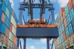 Uferkran hebt Behälter während der Frachtoperation im Hafen an Stockfotografie