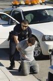 Ufficiale di polizia Arresting Young Man Fotografie Stock Libere da Diritti