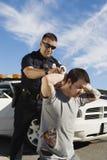Ufficiale di polizia Arresting Young Man Immagini Stock Libere da Diritti
