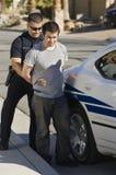 Ufficiale di polizia Arresting Young Man Immagini Stock