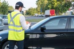 Ufficiale di polizia che dà un'indennità per la violazione di parcheggio Immagini Stock Libere da Diritti