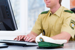 Ufficiale di polizia che lavora allo scrittorio nella stazione Fotografia Stock