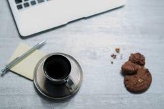 Ufficio che lavora vista da tavolino con il computer portatile, il blocco note ed il caffè con il biscotto Fotografie Stock Libere da Diritti