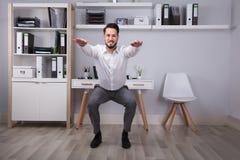 Ufficio di Doing Workout In dell'uomo d'affari fotografia stock
