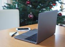 Ufficio di legno dell'albero di Natale della sfuocatura del computer portatile Fotografia Stock Libera da Diritti