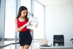 ufficio Donna di affari che sta alla grande finestra Ufficio moderno leggero Vestito in maglione rosso e gonna nera Cartella dell Fotografia Stock Libera da Diritti