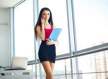 ufficio Donna di affari che sta alla grande finestra Ufficio moderno leggero Vestito in maglione rosso e gonna nera Cartella dell Fotografie Stock