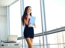 ufficio Donna di affari che sta alla grande finestra Ufficio moderno leggero Vestito in maglione rosso e gonna nera Cartella dell Immagine Stock Libera da Diritti
