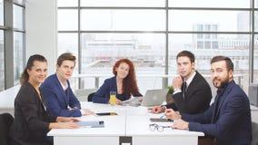 Ufficio e concetto di lavoro di squadra - gruppo di gente di affari che ha una riunione e pollici di rappresentazione su video d archivio