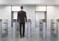 Ufficio entrante dell'uomo tramite cancello girevole Immagini Stock Libere da Diritti