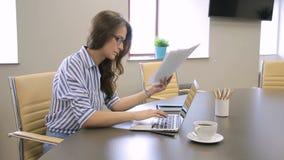 In ufficio la donna esamina i documenti con i grafici e stampa sul computer portatile video d archivio