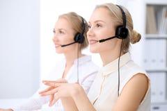 Ufficio luminoso della call center Due donne bionde in una cuffia avricolare Immagine Stock Libera da Diritti