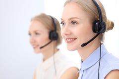 Ufficio luminoso della call center Due donne bionde in una cuffia avricolare Fotografia Stock