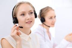 Ufficio luminoso della call center Due donne bionde in una cuffia avricolare Immagine Stock